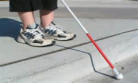 Photo of a child's feet in sneakers standing on a one-step platform with a while cane for the blind out in front