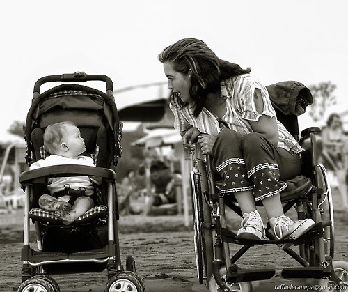 Baby carriage next to a wheelchair, both viewed from the front, baby in carriage, young adult woman in wheelchair, turned to her left to talk to the baby, with the baby looking at her