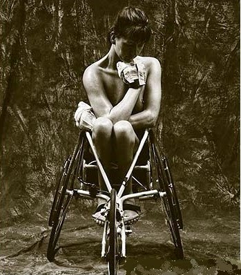 sepia toned photo of a naked woman in a racing wheelchair, arms wrapped around herself, viewed from the front