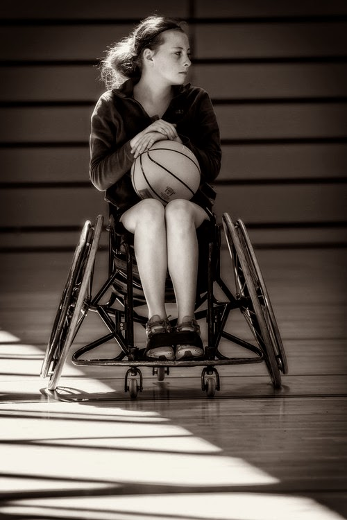 Young woman viewed face-on, sitting in a sports wheelchair with cambered wheels, clutching a basketball
