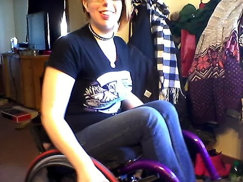 Photo of a young woman in a manual wheelchair doing a wheelie and smiling