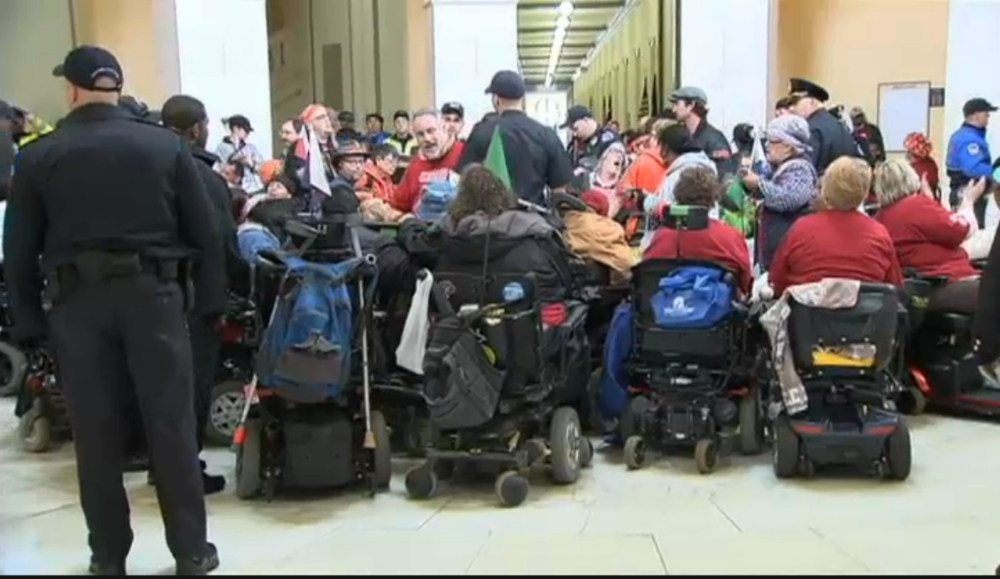 Protesters in wheelchairs viewed from behind, indoors