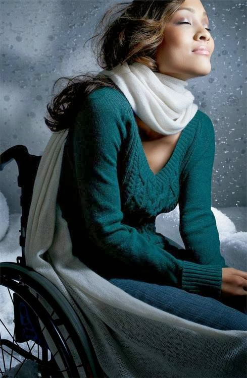 Photo of a woman sitting in a manual wheelchair, wearing a turquoise sweater, white scarf. She has her eyes closed and is facing to the right