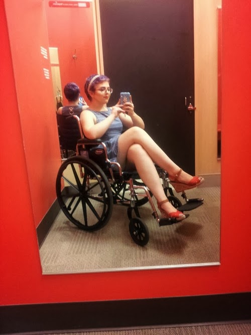 Young woman sitting in manual wheelchair, legs crossed, taking a selfie with a phone camera, viewed in a mirror