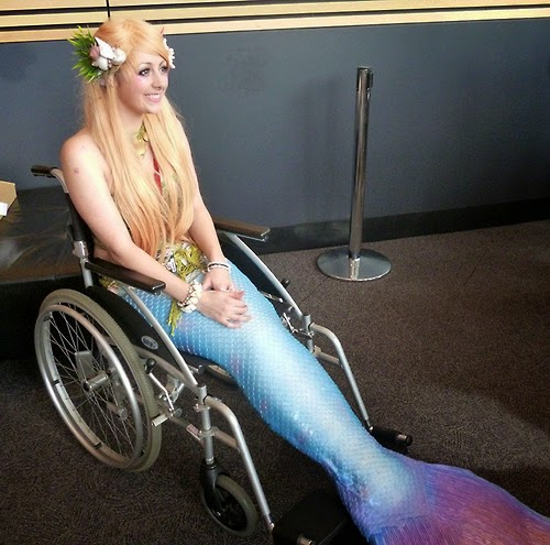 Photo of young woman with long blonde hair and a mermaid costume on her lower body - she is seated in a wheelchair