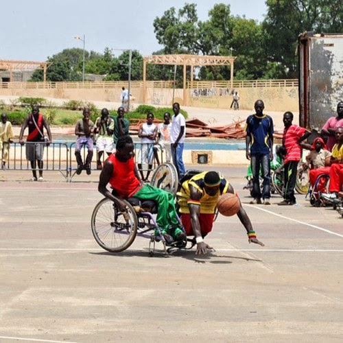 Photo of two African young men playing basketball outdoors. One is in a wheelchair, the other is not Other people are watching them play