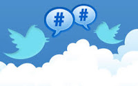 Illustration of two Twitter logo bird facing each other above clouds, with talk balloons containing hashtag symbols