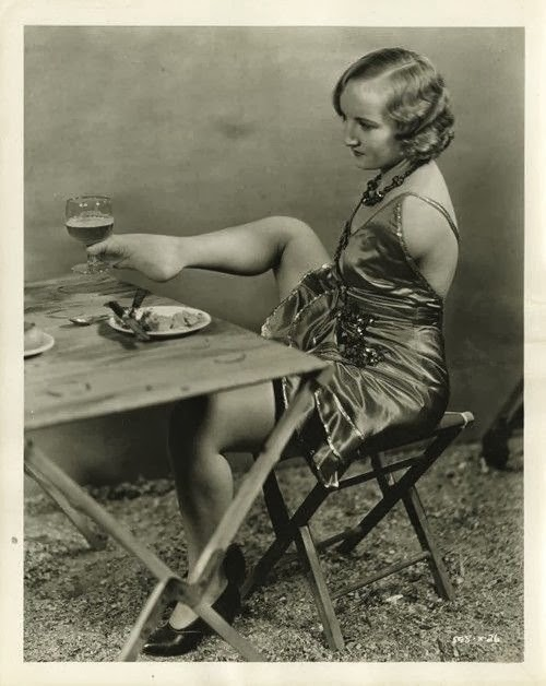 """vintage black and white photo of """"flapper"""" woman without arms lifting glass of wine with her foot"""