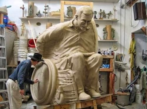 Man working on a large-scale sculpture of a man in a wheelchair