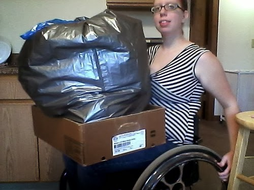 young woman in wheelchair with full garbage bag, inside shallow cardboard box, on lap.