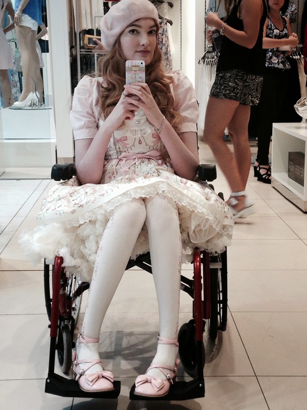 Young white woman sitting in a wheelchair taking a selfie with a smartphone, wearing a white frock dress and light pink hat