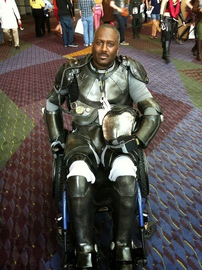 African-American man in full body armor sitting in a wheelchair