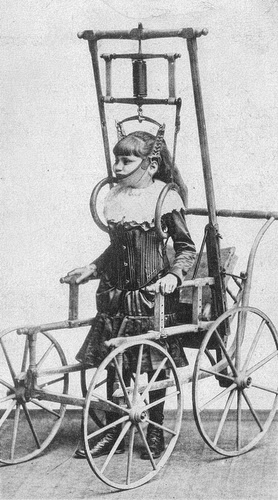 Vintage black and white photo of a young girl in a complex wheeled standing frame