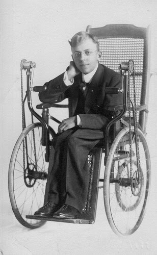 Vintage black and white photo of a young man in a dark business suit sitting posed in a old-fashioned wheelchair