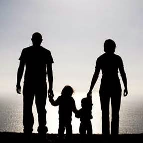 Silhouette of parents and two small children