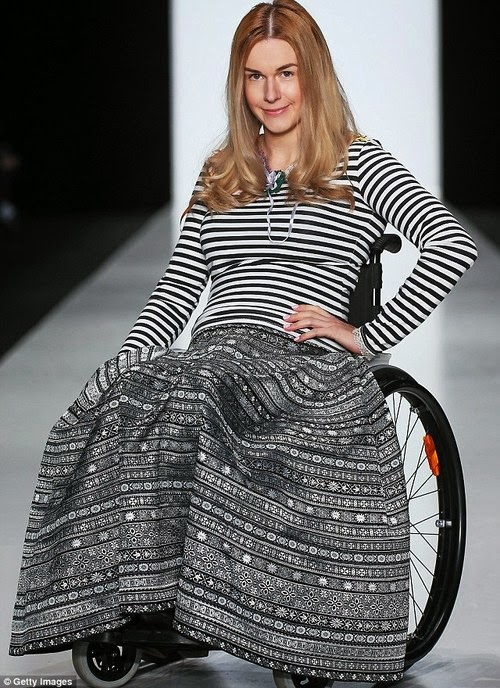 woman in wheelchair fashion show pose, blonde hair, striped top and ornately patterned dress, all in black and white coloring