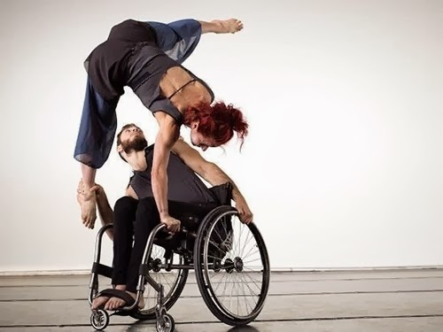 Man in wheelchair dancing acrobatically with woman