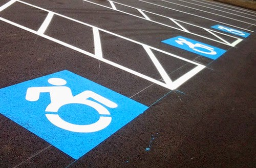 Color photo of three accessible parking spaces featuring the new wheelchair symbol design