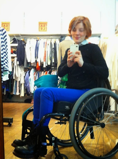 Young woman with red, medium-lenght hair sitting in a dark grey manual wheelchair, taking a selfie. Has boots and bright blue pants and a dark blue sweater