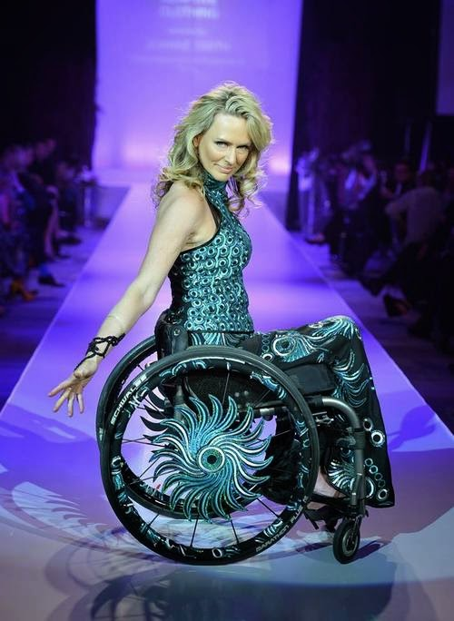 Blonde woman in a manual wheelchair, viewed from the side. She is dressed in a aqua and blue patterned dress that matches decorative patterns on her chair