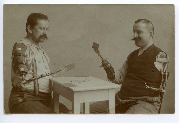 Old brown-tone photo of two men, both with prosthetic arms, playing cards.