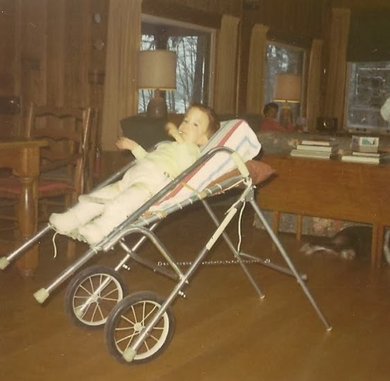 young child in two-leg cast held in a reclined wheeled carrier, being pushed by a teenage girl