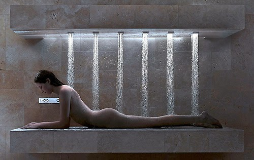 Woman lying on her stomach, propped up on her arms, in a shower with six nozzles spaying water over her whole body