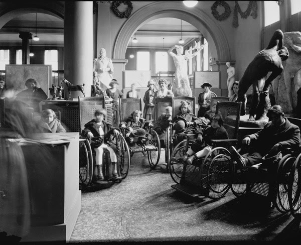 black and white photo of the inside of a museum with several children in wheelchairs