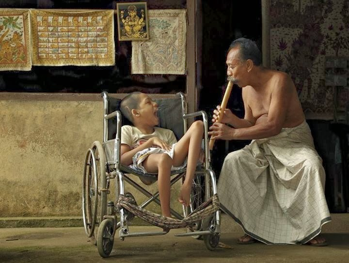 small boy in wheelchair, man crouched down, playing flute for the boy