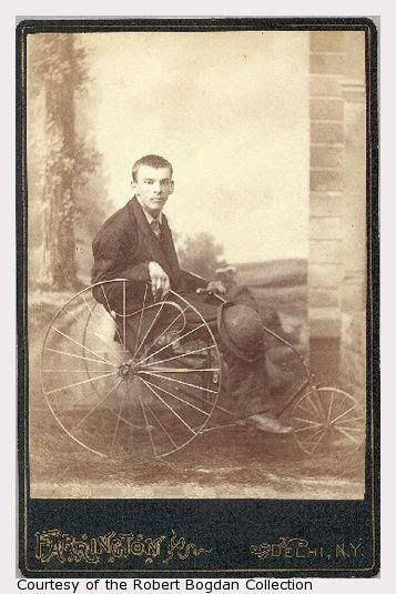 Vintage, sepia tone photo of a young man in an old-style wheelchair, wearing a suit and holding a cane and bowler hat