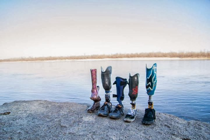 Five prosthetic legs, different sizes, different colors and patters, displayed in a row, on a flat rock surface next to a calm lake