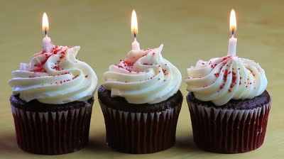 Three cupcakes in a row, with a lit candle in each one
