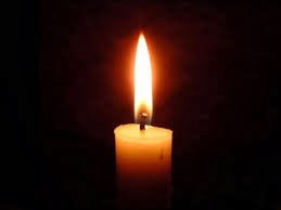Single lit candle against a dark background