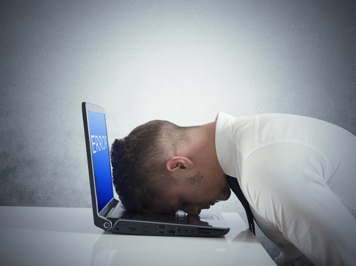 Photo of a man with his forehead planted onto an open laptop computer's keyboard
