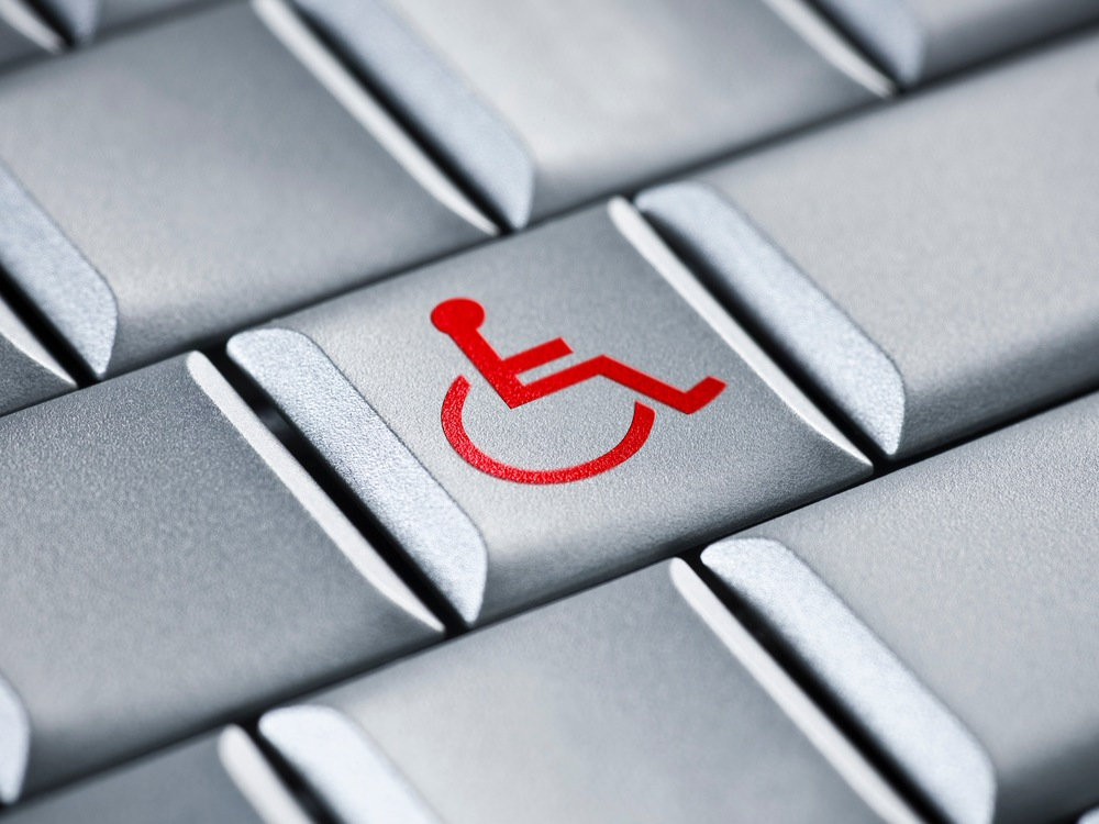 Close up photo of a grey computer keyboard with a red wheelchair symbol on the center key