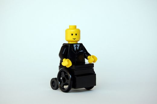 Lego figurine with yellow skin wearing a black suit and tie, sitting in a black Lego wheelchair