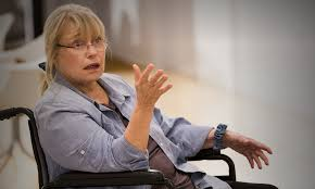 TV still image of a middle aged blonde woman sitting in a wheelchair, talking and gesturing