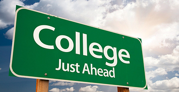 "Photo of a green highway-type sign with white letters reading ""College Just Ahead"", in front of a partly cloudy sky background"