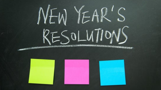New Year's Resolution written in white chalk on a blackboard, with three colored post-it's below