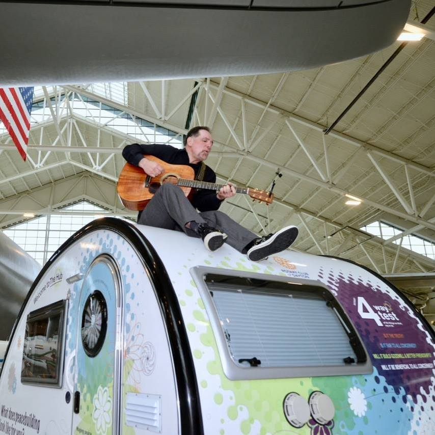 Rotarian Peace Troubadour, Jerry Leggett performs for peacebuilders beneath the Spruce Goose at the Evergreen Aviation and Space Museum in McMinnville, Oregon. (Photo credit: Patsy Ferrell,©2017, Used with permission)