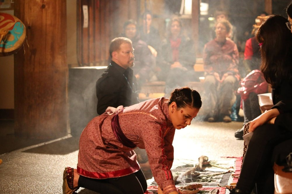 Lindsay Katsitsakatste Delaronde and Aaron Rice kneel on bandanas of red, white, black and yellow and laid out cedar boughs, braids of sweetgrass and bundles of sage while T'uy't'tanat Cease Wyss drums and sings a Squamish song of welcome. (photo: Kwakwee Baker)