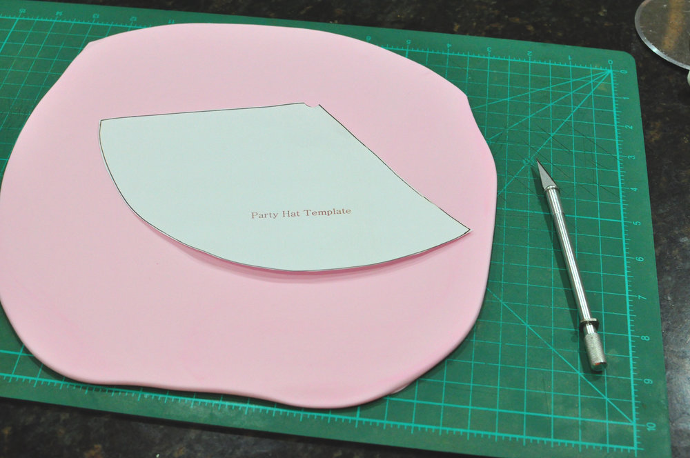 Roll your fondant out.  I roll mine about 1/4 of an inch thick - thick enough so that when you form the hat the edges are thick enough to stick well together.  Place your template on fondant and cut that baby out!!