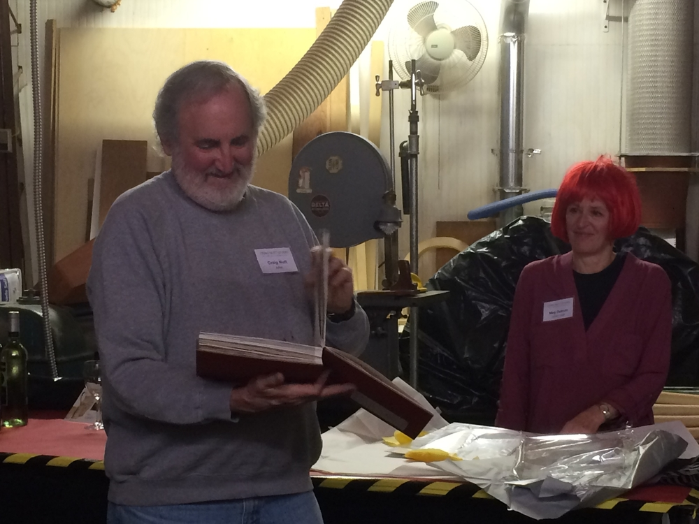 "Meg Ostrum presents me with ""The Book of Craig."" Barbecue photos by  Jenifer Simon  of CERF+."