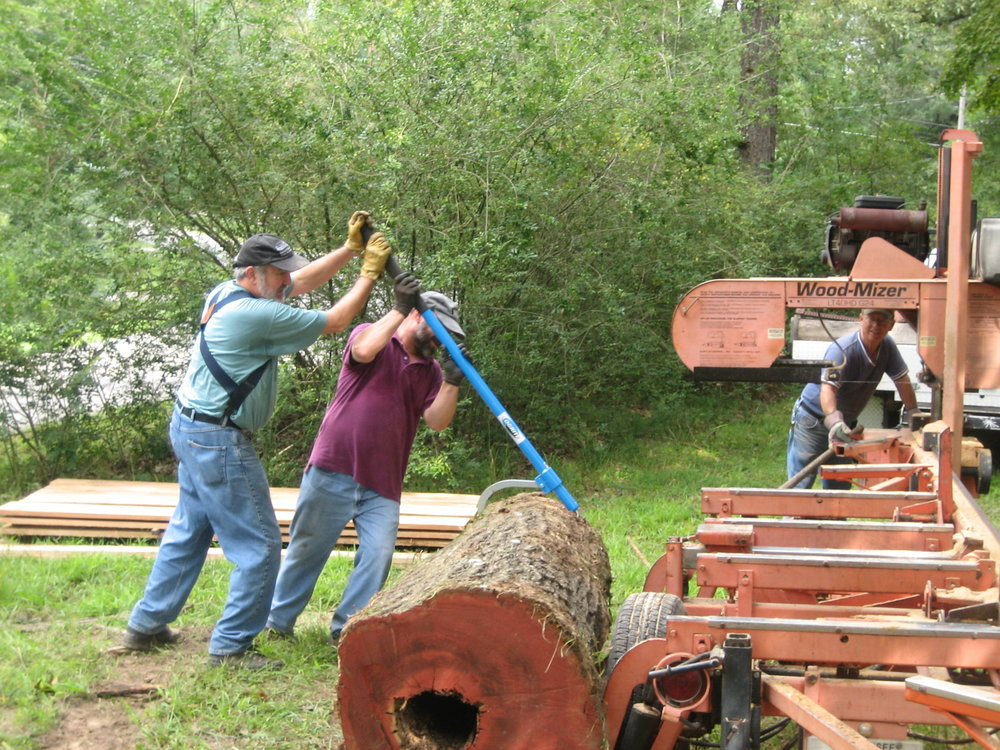 Sawing logs This is from a previous milling. Master potter,  Timothy Weber  is helping me roll a log up to the portable sawmill.