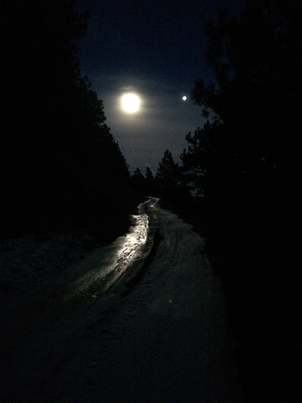 Full moon lighting on an icy dirt road. Venus to the right of the moon. Super cool.
