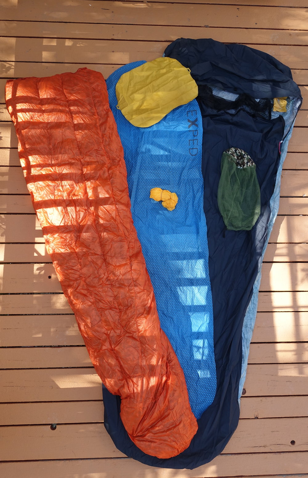 Here's my sleep system. I use a Borah Gear bivy, Exped pad and pillow, and an Enlightened Equipment quilt. The small yellow ball is a bag used to inflate the sleeping pad. There's a mosquito net to help with both sleep and on-bike insect encounters. Inside the bivy, you can see a small yellow pocket. I stuck that to the inside of the bivy and keep ear plugs in it.