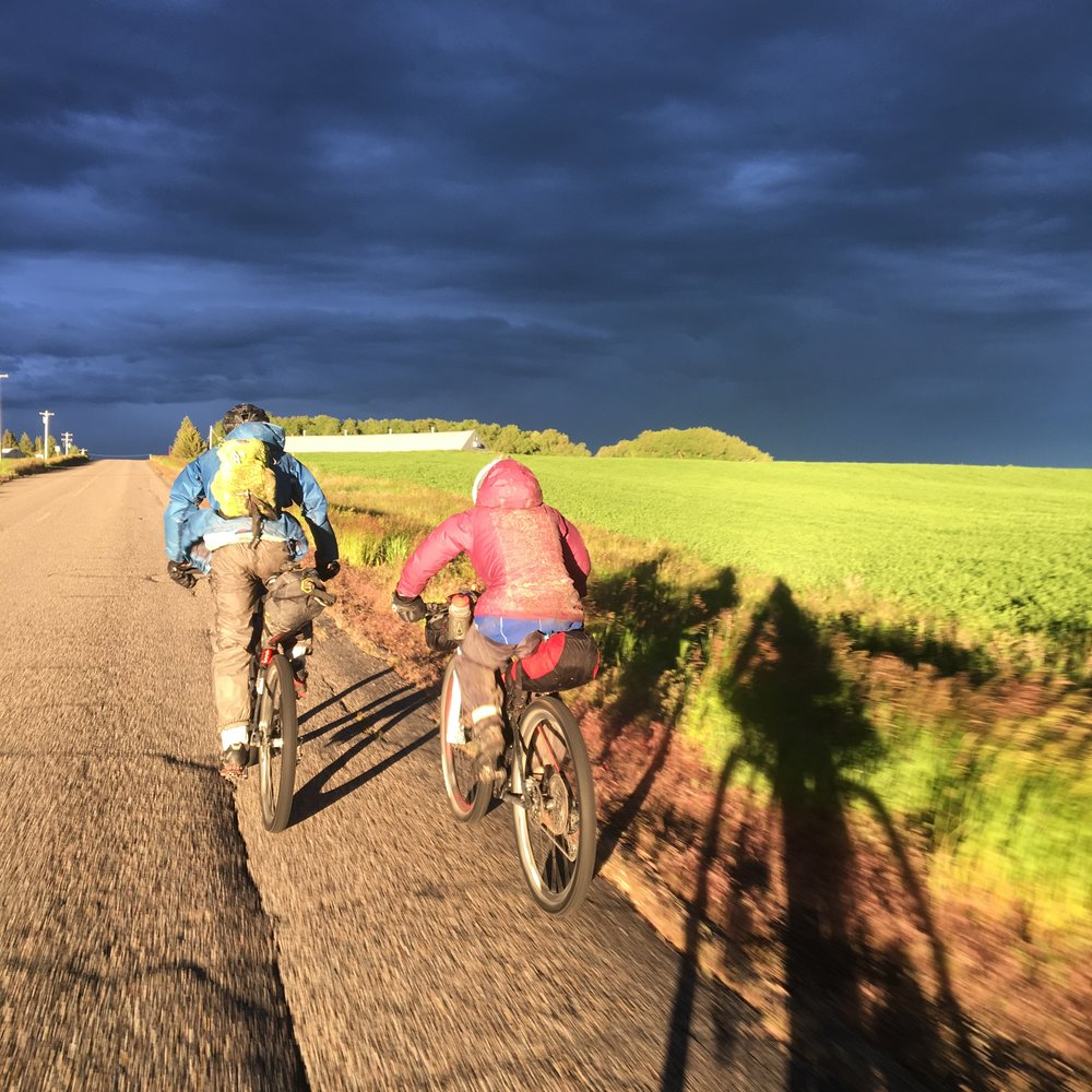 Trippy light in Idaho as storms sit on the Tetons ahead and the setting sun illuminates my riding partners.