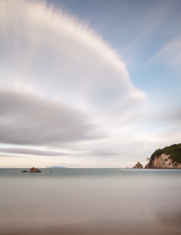 Clear Air I, Evening Light Long exposure seascape with clouds stretching in early evening light over the beach and heads at Whangamata with distant island off the Coromandel Peninsula, New Zealand.