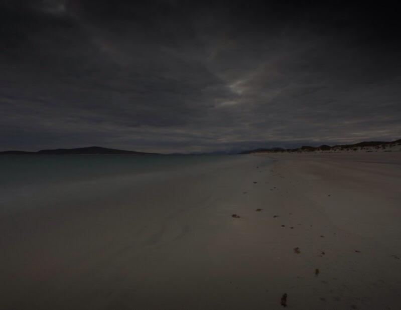 Night sweeps dark islands on a vast and empty shore, West Beach, Isle of Berneray, Scotland.
