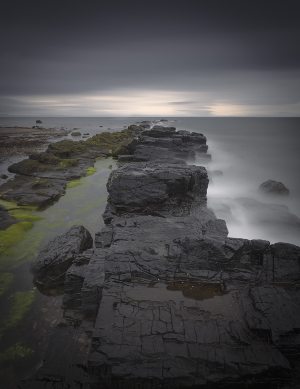 A black basalt dyke stretches out into a stormy sea under grey and threatening skies on the Isle of Arran off the West Coast of Scotland